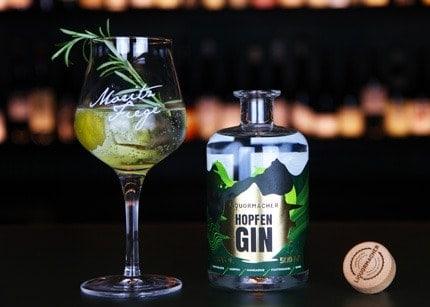 Glasflasche und Glas Liquormacher Hopfen Gin mit Rosmarin und Zitrus